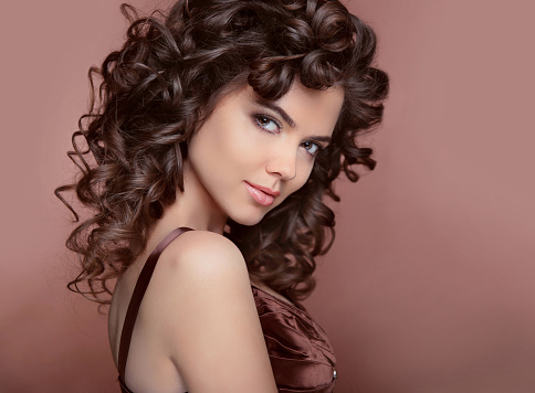 Healthy hair. Beautiful young smiling woman with long curly hair